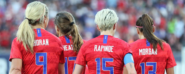 women's soccer players Lindsey Horan, Tobin Heath, Megan Rapinoe and Alex Morgan, seen from behind.
