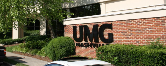 Universal Music Group (UMG) logo on a brick wall.