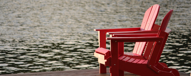 red adirondack chairs on a dock by water.