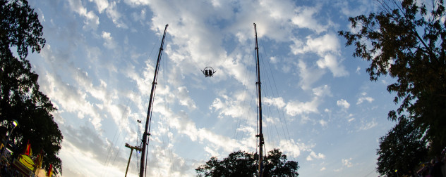 a slingshot-style ride seen against a twilight sky with trees.