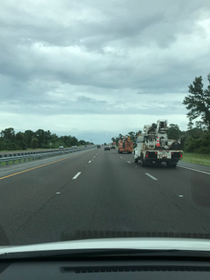 utility trucks on the highway under an overcast sky.