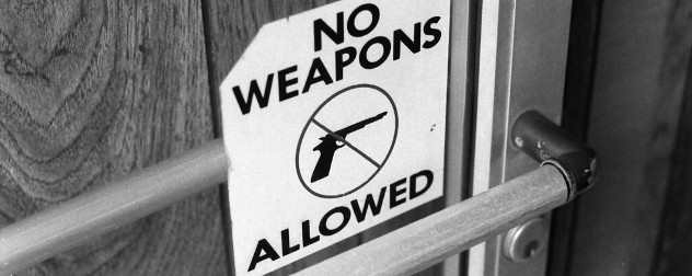 No Weapons Allowed sign on door, with no symbol over an image of a gun.