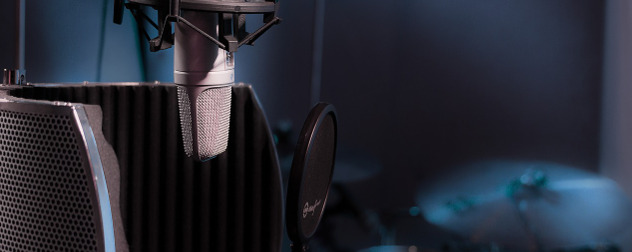 detail of microphone in recording studio with cymbals in background.