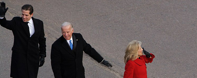 Hunter Biden, Joe Biden and Jill Biden waving while walking in a parade.