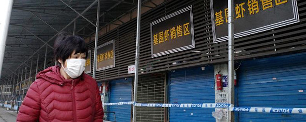 a person in a medical face mask walks by a shuttered market in Wuhan, China.