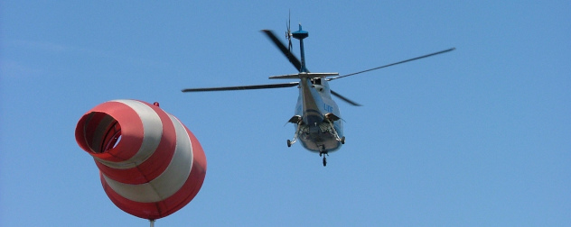 Sikorsky S-76C helicopter flying away, wind sock in foreground.