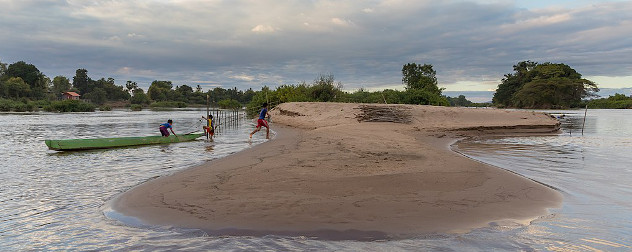 Three children running from their boat up a sand bank on the Mekong River near Si Phan Don.