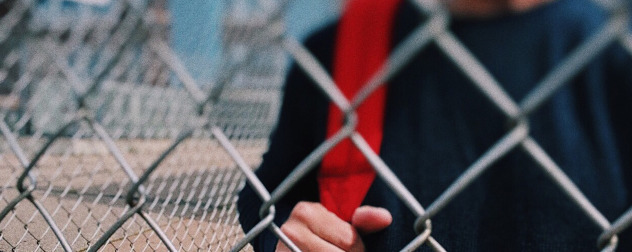 detail of student with red book bag strap behind chain-link fence, presumably at school.