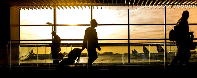 silhouette of people walking through an airport against a window.