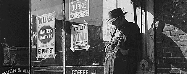 black and white image of a man in a hat and overalls leaning against a store covered in 'to lease' signs, among Depression-era heavy unemployment.
