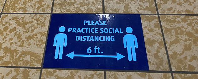 grocery store sign that reads 'please practice social distancing' with two people separated by 6 feet.