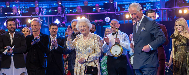 Queen Elizabeth II on stage with Prince Philip and various musicians and entertainers at Royal Albert Hall.
