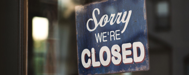 wooden sign that says 'Sorry, We're Closed' in a business window.
