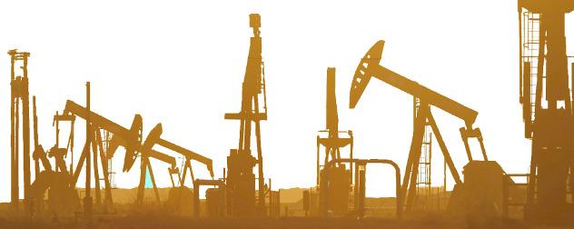 oil rigs seen in silhouette.
