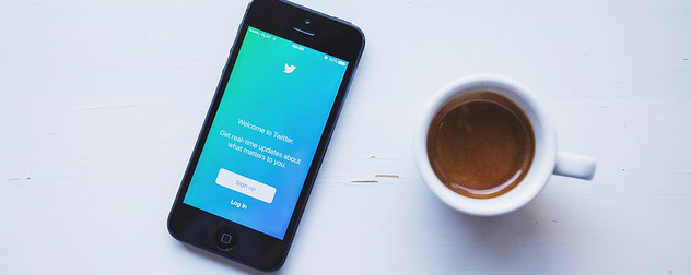 phone displaying Twitter app next to a cup of coffee.