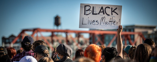 protesters, including one holding a sign that says 'Black Lives Matter,' at a protest following the death of George Floyd.