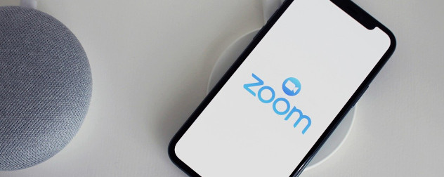 Google Home assistant and smartphone displaying a logo for the Zoom app.