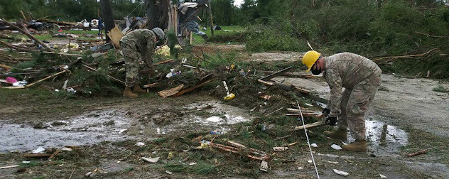 Members of the North Carolina National Guard pick through post-hurricane debris.