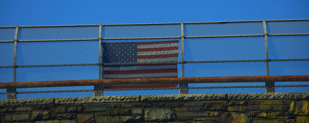 American flag hung on overpass fence.