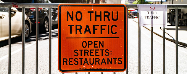 sign on a barricade that reads 'No Thru Traffic, Open Streets, Restaurants.