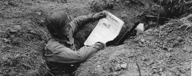 Two WWII GIs in a foxhole, one reading an issue of Stars and Stripes and the other reading mail.