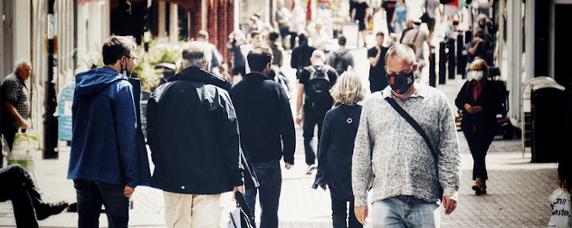 people walking on the street, some masked, in London.