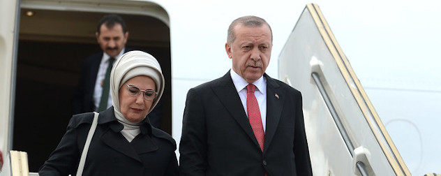 President of Turkey, Recep Tayyip Erdogan, descending stairs to exit an airplane.