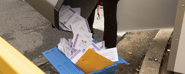 absentee ballots being poured into a bin ahead of Election Day.