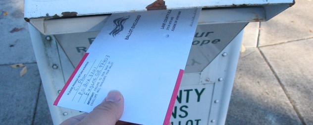 Voter putting a sealed ballot into a ballot return box, Lane County, Oregon.