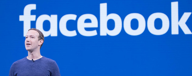 Facebook founder Mark Zuckerberg speaking in front of a blue slide with Facebook's name.