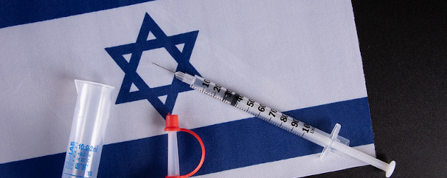syringe and other vaccine supplies against a backdrop of Israel's flag.