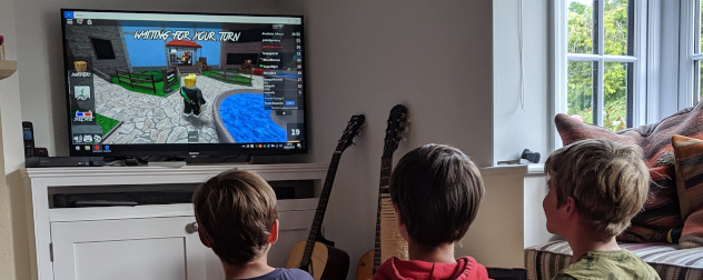 kids playing Roblox on a large screen.